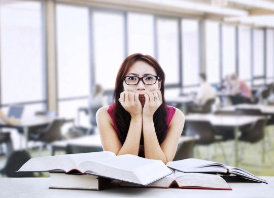 Young female student is afraid while she's studying for her exams in library